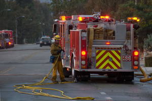 7:06 PM - A firefighter packs up his hose. Nancy Hamlett.
