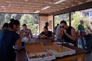 Volunteers eat pizza in the old outdoor classroom. Nancy Hamlett.